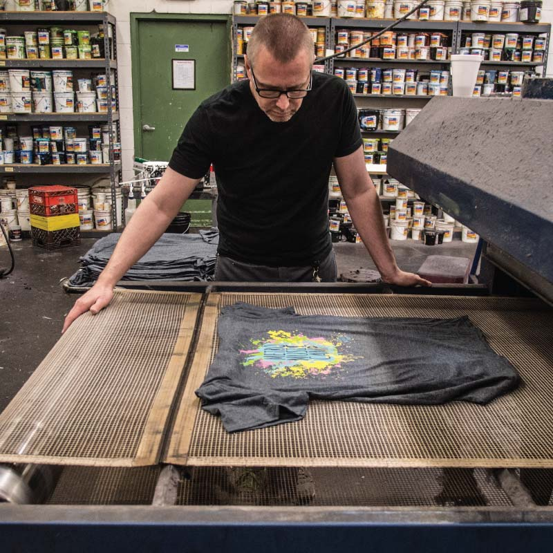 A person screen printing t-shirts