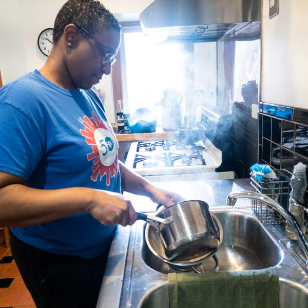 A person washing dishes in a shared kitchen
