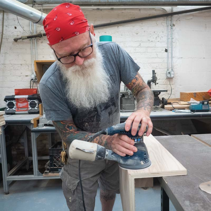 A person sanding in a wood shop